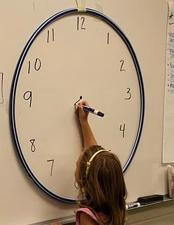 Student working on giant clock face in the classroom